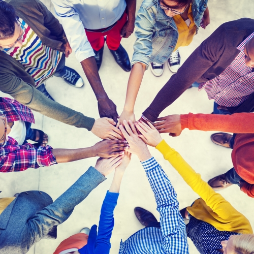 Stock photo of a group of people in a circle with one hand pointing to the centre